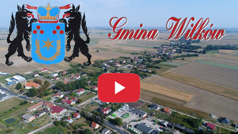 Obraz przedstawia widok na Gminę Wilków z lotu ptaka. Dodatkowo umieszczono herb Gminy oraz ozdobny napis Gmina Wilków. Obraz jest linkiem do serwisu YouTube
